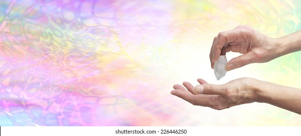 Crystal Healer holding terminated quartz in one hand pointing it at open palm with psychedelic pastel colored energy in background