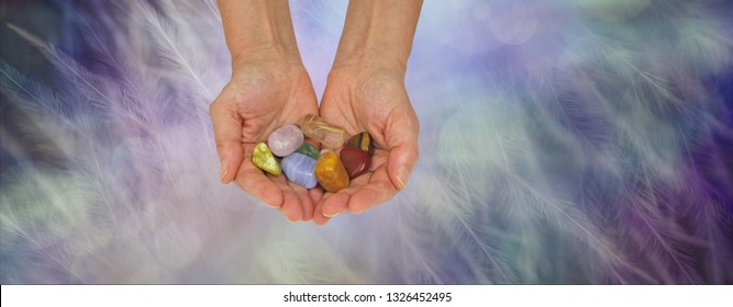 Crystal healing practitioner offering selection of tumbled healing stones - female crystal therapist with cupped hands filled with a variety of crystals on an ethereal feathered background