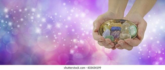 Crystal healing therapist banner - female crystal healer holding and offering brass dish with a selection of healing crystals on a pink purple colored sparkling wide background with copy space