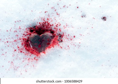 crystal heart lies on the snow in the blood, drops of blood on the snow, copy space, close up, selective focus