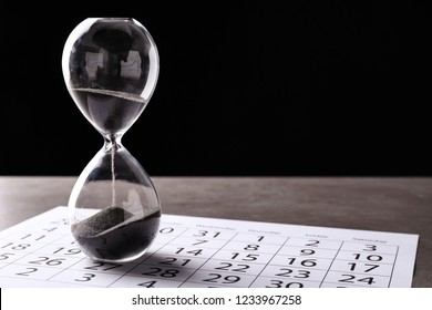 Crystal hourglass with calendar on table. Deadline concept