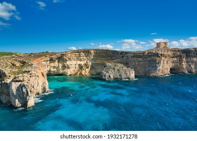 The Crystal Lagoon with clear azure-coloured water. View of the coastline and the turquoise blue water. The Saint Mary's Tower on the cliff. bathing holiday and snorkeling on the island Comino, Malta.