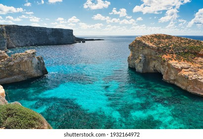 The Crystal Lagoon: View of the coastline with steep cliffs and beautiful clear azure-coloured water in summer. A mediterranean paradise for snorkeling and diving on the island Comino, Malta.