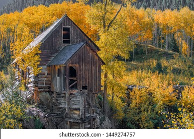 The Crystal Mill on the Crystal River in the Mountains near Marble, Colorado and Redstone, Colorado, surrounded by orange Aspen Trees and foliage on a fall morning.
