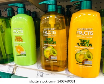 Crystal, Minnesota - May 19, 2019: Garnier Fructis brand shampoo and conditioner hair care products on the shelf at a Target store. Sleek and Shine and Triple Nutrition