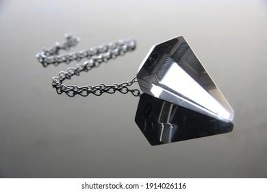 Crystal pendulum, smoky quartz, with reflection on bright background