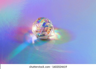 Crystal prism Refracting light in vivid rainbow colors. glass prism on holographic background. spiritual healing crystal practice. Feng Shui, Good energy flow concept