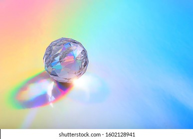 Crystal prism Refracting light in vivid rainbow colors. glass prism on holographic background. close up. copy space