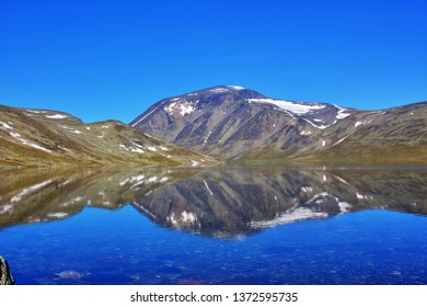 Crystal pure lake water reflects mountains and pleasant sky in Jotunheimen in Norway
