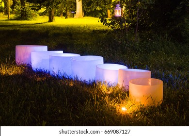 Crystal singing bowls. Meditation and Budha in the park. Light in diferrent colours.