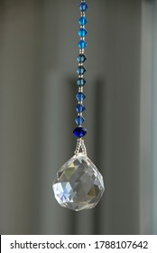 Crystal suncatcher with blue beads by the window