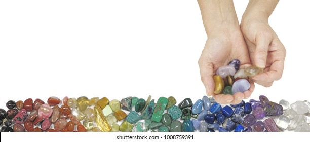 Crystal Therapy Website Banner - female hands on right side offering a selection of tumbled stones against a white background and row of chakra colored healing stones beneath