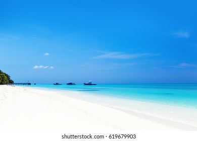 Crystal turquoise sea with jetty and boats on Maldives island, travel destination.