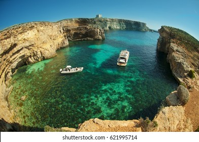 The Crystal water of Blue Lagoon - Comino island in Malta. Spring. Two boats on the water