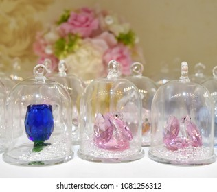 Crystal work in shape of pink swan and blue rose in a glass box as a gift souvenir or home shelf decoration