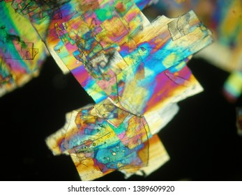 Crystallized liquid crystal under polarized light microscope forming a rainbow texture. Abstract squares filled with rainbow colors.