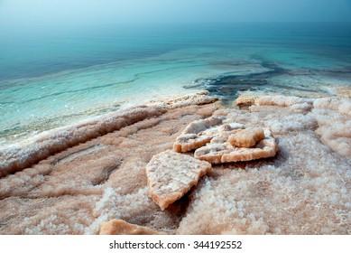 Crystallized salt cover the beach of Dead Sea. Jordan.
