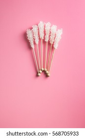 Crystallized sugar on wooden stick on pink background. Top view.