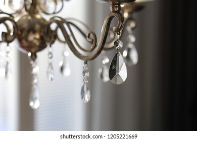 Crystals of a beautiful living room chandelier. Gorgeous and stylish photo with harmonic black, brown and white colors. Luxurious home decoration element made of glass and metal.
