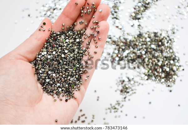 Crystals. Crystal rhinestones in the hand on a white background. Beautiful shiny sparkling silver rhinestones in her hand. isolated. Jewelry, rhinestone, shiny stones.