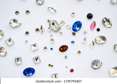 Crystals. Crystal rhinestones on a white background. Beautiful shiny sparkling multi colored rhinestones. Isolated. Jewelry, rhinestones, shiny stones.