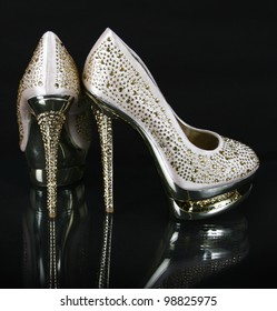 crystals encrusted gold shoes on black background