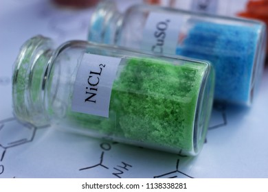 Crystals of green nickel chloride in a glass jar. The substance is used in electroplating.