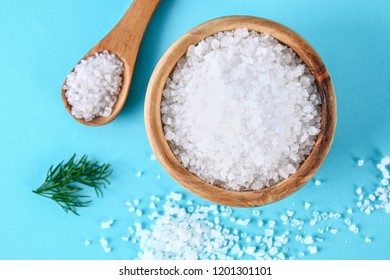 Crystals of large sea salt in a wooden bowl and spoon and dill on a blue table. Background for advertising salt. Table salty. Salted food.