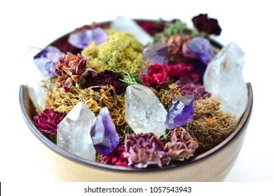 crystals and moss with dried flowers in bowl with crystals on white background
