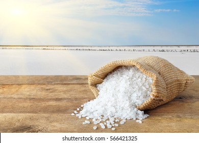 Crystals of sea salt in sack on table with salty lake with sun in the background