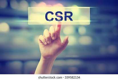 CSR - Corporate Social Responsibility concept with hand pressing a button on blurred abstract background
