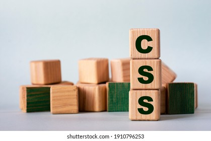 CSS (Cascading Style Sheets) - acronym on wooden cubes on a background of colored block on a light background. Internet concept