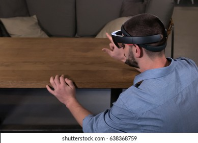 CU young adult Caucasian male using holographic augmented reality glasses in trendy office. Future business concept