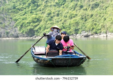 CUA VAN VILLAGE, VIETNAM - May 24, 2011: Vietnamese woman in the mask and traditional Vietnamese cap rows a small boat with tourists in Halong Bay (UNESCO World Heritage Site)