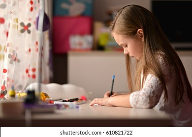 cuacasian little cute girl write a paper