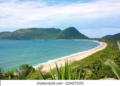 CUALDRON BEACH, FLORIANOPOLIS, SANTA CATARINA, BRAZIL. SOUTH AMERICA.  View of Caldeirão beach from a hill. Sunny day of summer in Floripa. Mirante do Morro das Pedras. Destination in Latin America.