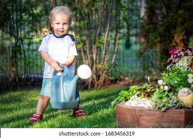 Cuate adorable caucasian blond little toddler boy in watering flowerbed flower pot with green plastic can outdoors. Fun baby boy gardening plant at backyard countryside cottage on bright summer day.
