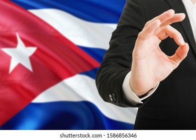 Cuba acceptance concept. Elegant businessman is showing ok sign with hand on national flag background.