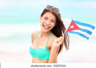 Cuba beach woman holding cuban flag during resort vacation travel on cuba. Beautiful young mixed race Asian Caucasian happy and smiling in bikini.