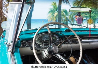 Cuba blue classic car park near the beach in havana with dashboard interior view