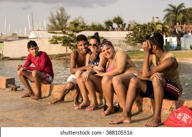 Cuba, Cienfuegos: Typical street scene with group of five young Cubans people smile, sit, relax on a bench and have fun in warm sunlight of late afternoon sunset. March 13, 2015