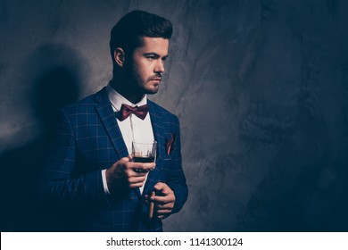 Cuba cigar expensive tobacco product cocktail liquor bar modern lifestyle concept. Close up photo portrait of serious confident guy holding glass in hand isolated gray background copy space