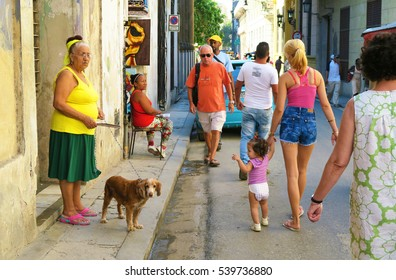 Cuba, Havana - 07 April, 2016: colorful scene from the life of ordinary people of Havana, Cuba, walking in the street among curious tourists, old, middle-aged, young people and babies