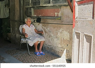 Cuba, Havana - 07 April, 2016: old caucasian Cuban grey-haired woman sitting in her home in Havana, smiling into the emptiness, in a complete delirium, with dementia