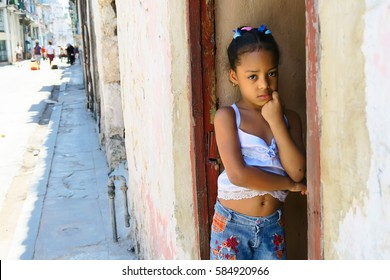 Cuba, Havana - 07 April, 2016: little latin american girl of African carnation in Havana, Cuba, standing and waiting for her mother from a beauty salon, in a typical street, on a normal spring day