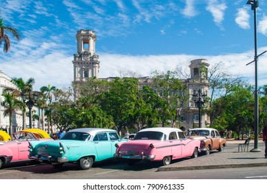 CUBA, HAVANA, 2017; Great Theatre of Havana Alicia Alonso in Cuba. Famous theater in Cuba. Old car under the theatre. Light pink and turquoise pontiac.