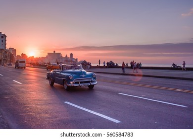 Cuba, Havana, March 8, 2016: sunset on El Malecon at the seaside while an oltimer taxi passes by. The street view of Havana is changing slowly with modern and old cars mixing on the road.