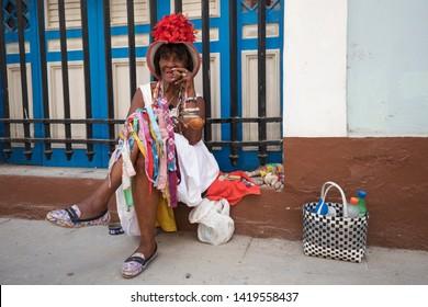 Cuba, Havana - May 11, 2017: old woman smokes typical cuban cigar in old part of Havana