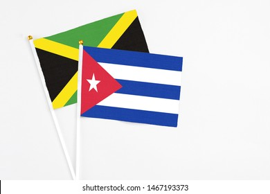 Cuba and Jamaica stick flags on white background. High quality fabric, miniature national flag. Peaceful global concept.White floor for copy space.