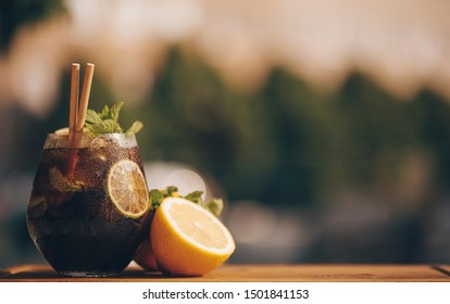 Cuba libre alcohol cocktail with golden rum, lemon juice, cola, lime and ice, dark bar counter background, bar tools, place for text